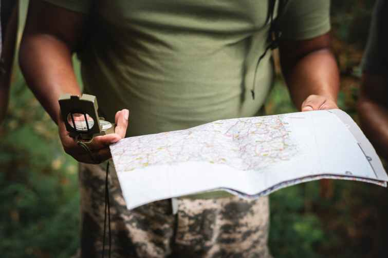 photo of person holding map and compass