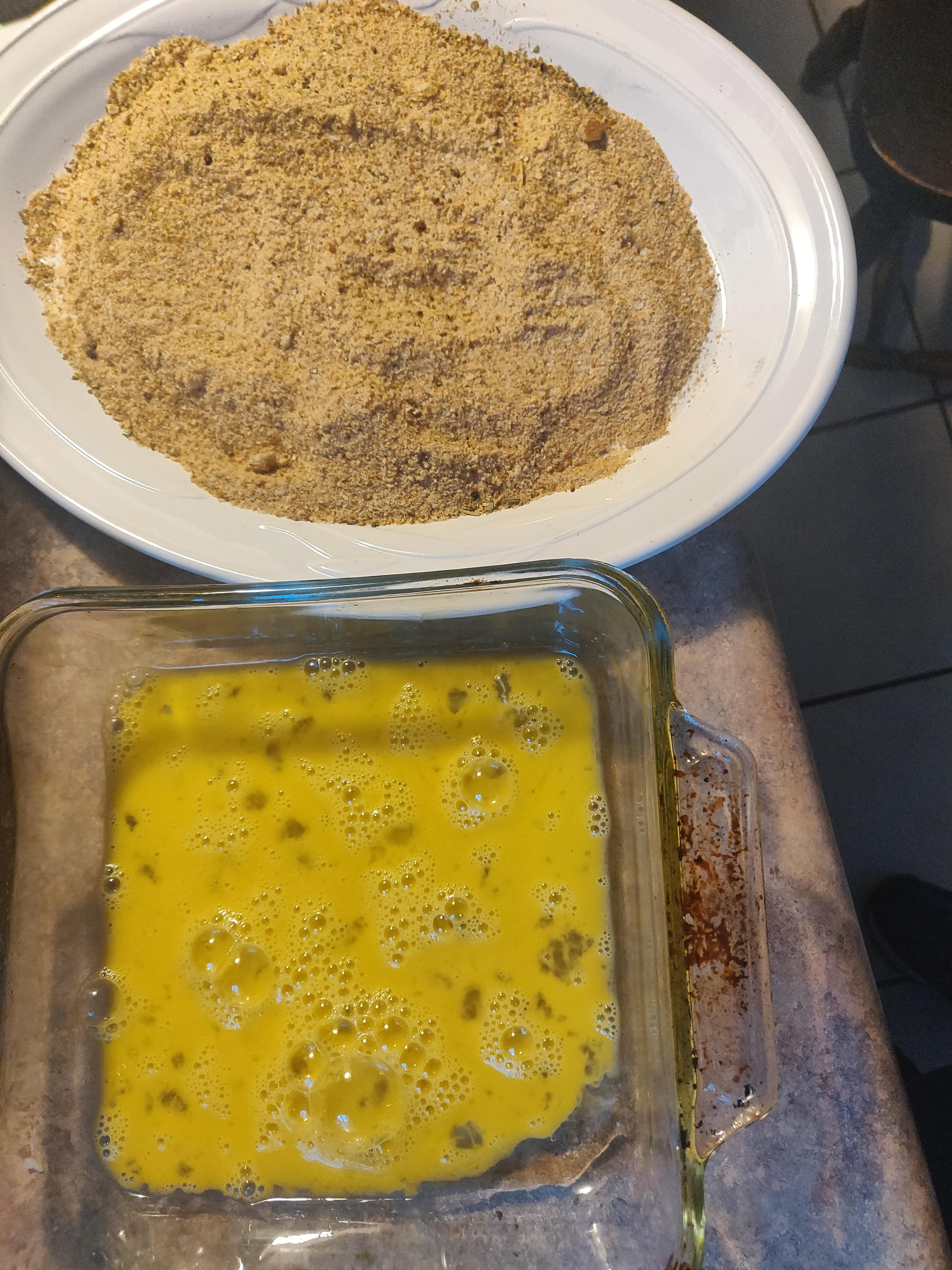 Breadcrumbs in a platter and scrambled whole eggs, ready to become the assembly line for the cutlets.