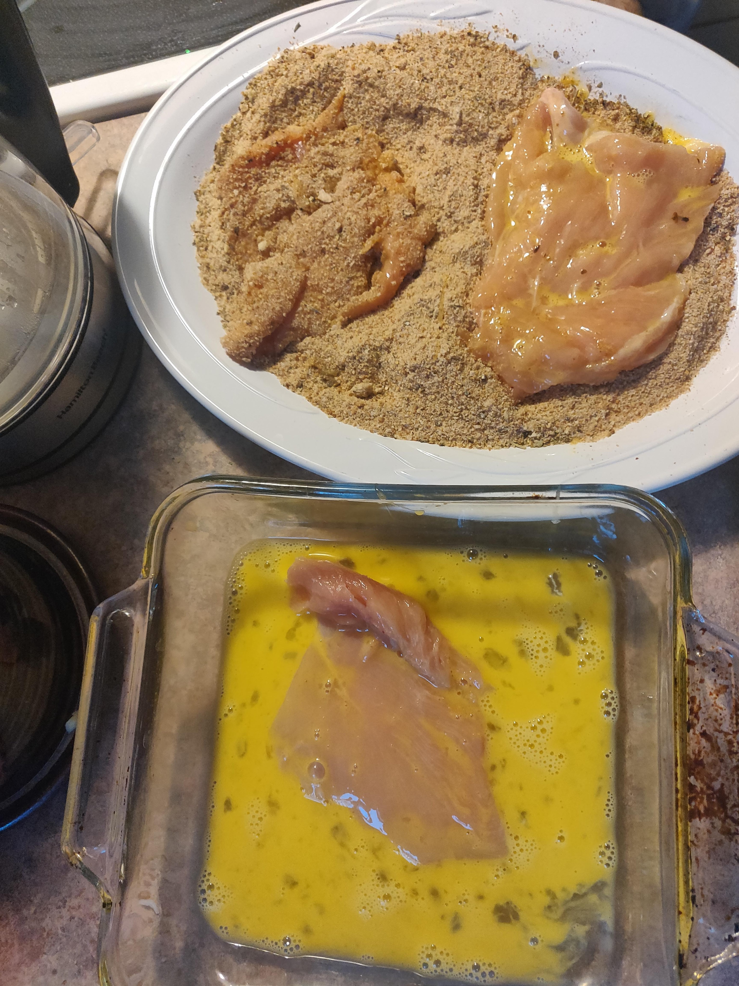 Progression of the cutlet workflow: A cutlet in the egg, a cutlet in the breadcrumbs (one side only), and a cutlet ready to go into the frying pan.