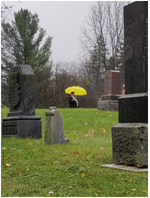 Canadian Veteran, viewed at a distance between gravestones at a cemetery.