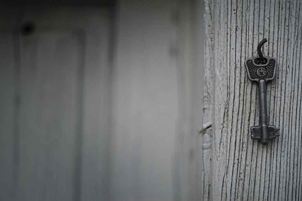 close up of a key hanging on a nail that's been hammered into a wall.