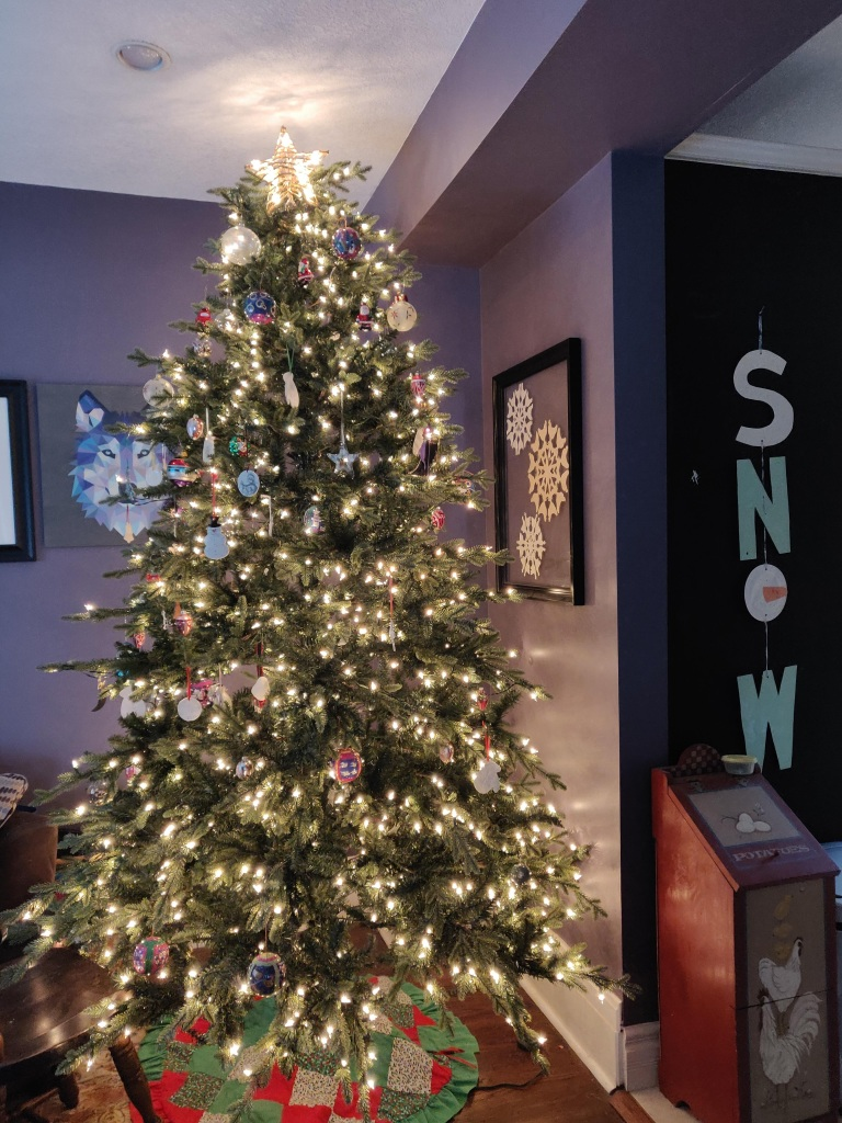 A Christmas tree lit with white lights, with a patchwork tree skirt.