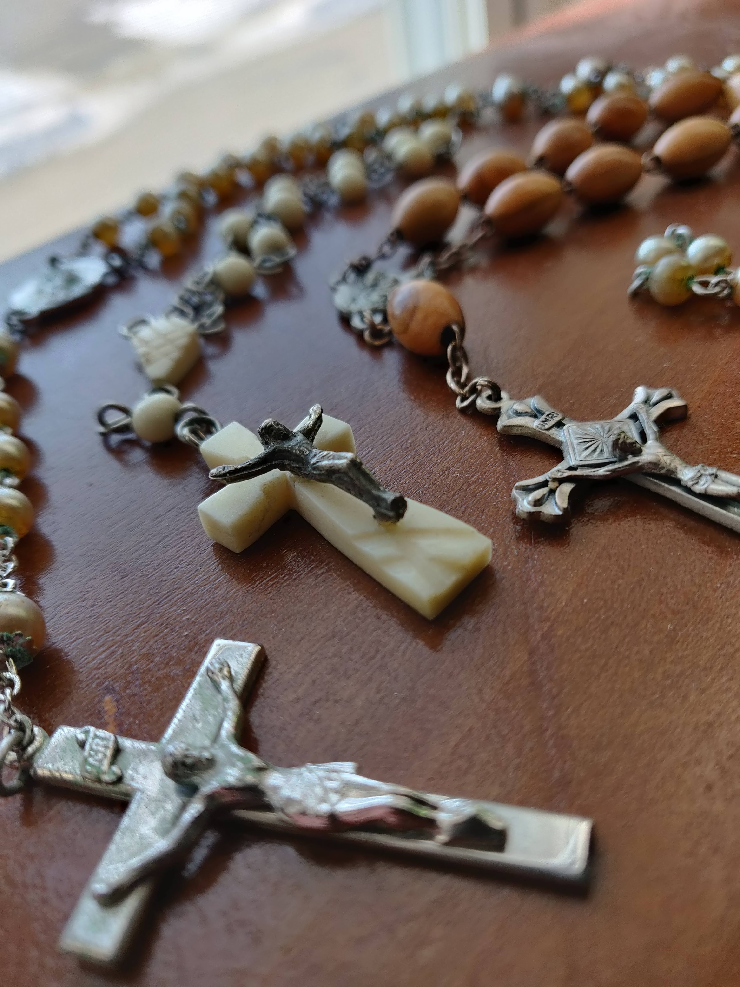 a close up of the crucifixes of three Rosary strings. One is a metal crucifix attached to a pearl-bead rosary, one is bone, attached to bone beads, and the third is wood beads with a metal crucifix.