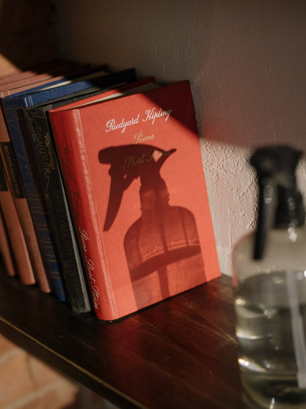 Light shining on a spray bottle of clear liquid that is casting a shadow on a shelf of vintage books.