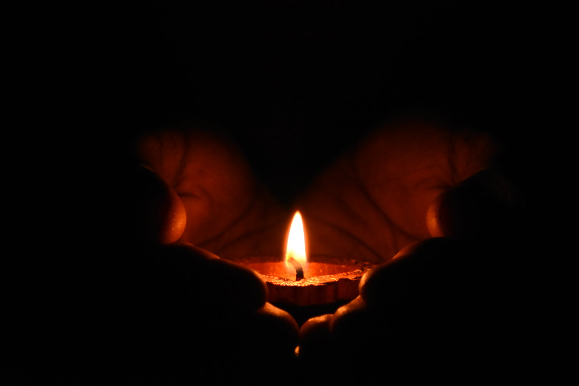 A candle held in cupped hands. The flame from the candle is the only light, casting shadow other than the skin touched by the flame's light.