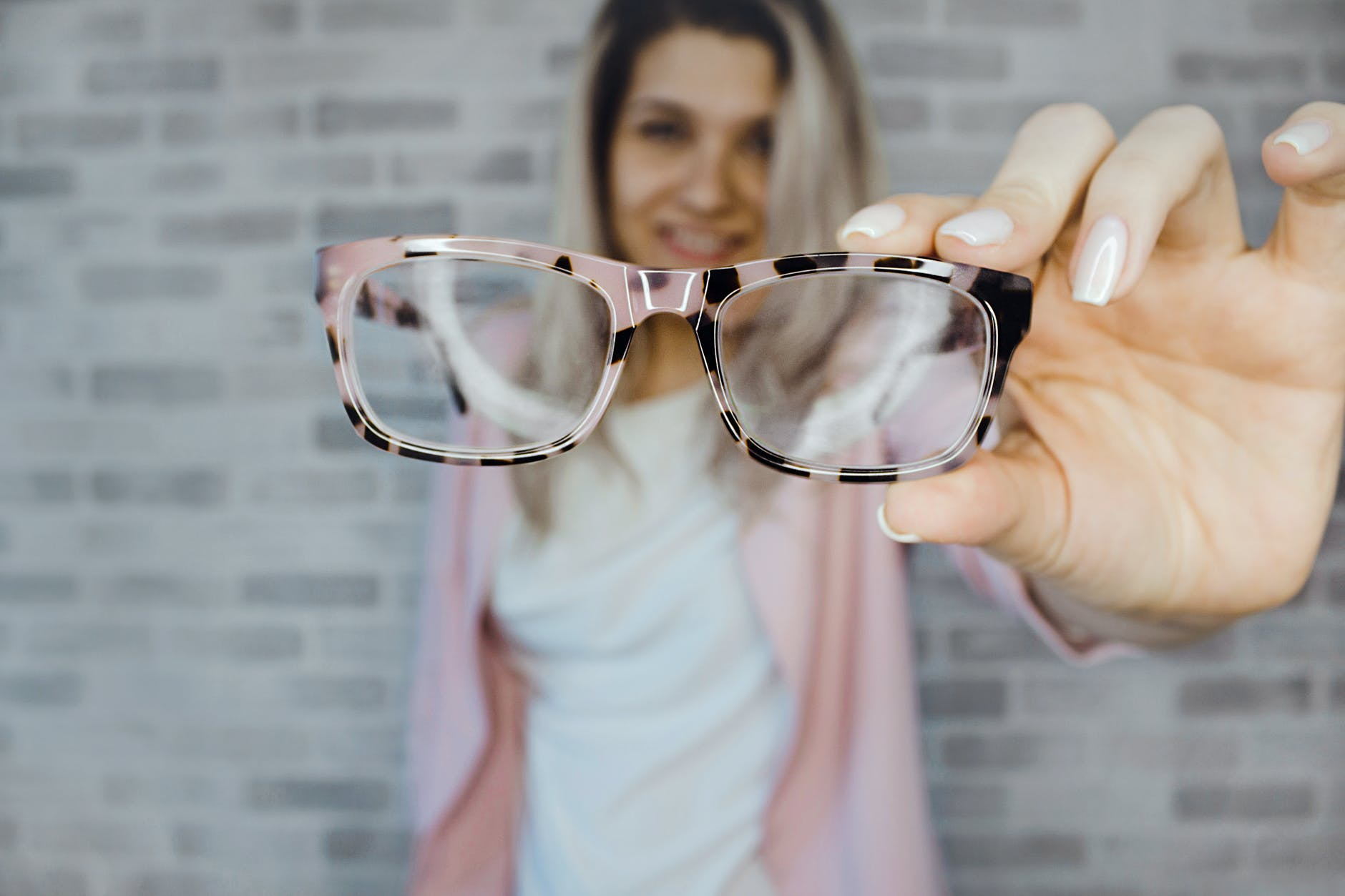 Woman holding glasses out in front of her. The glasses in the foreground have the focus, and she is blurred in the background.