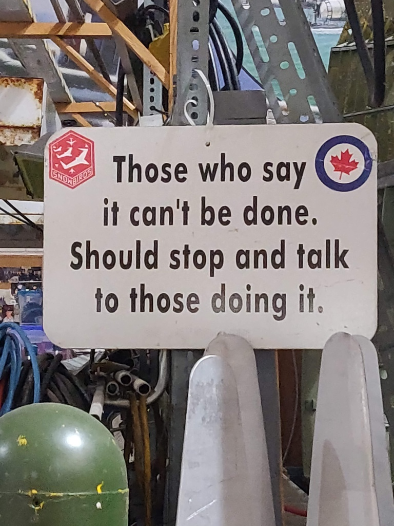 """Photograph of a sign from the Canadian Warplane Heritage Museum saying """"those who say it can't be done should stop and talk to those doing it."""""""
