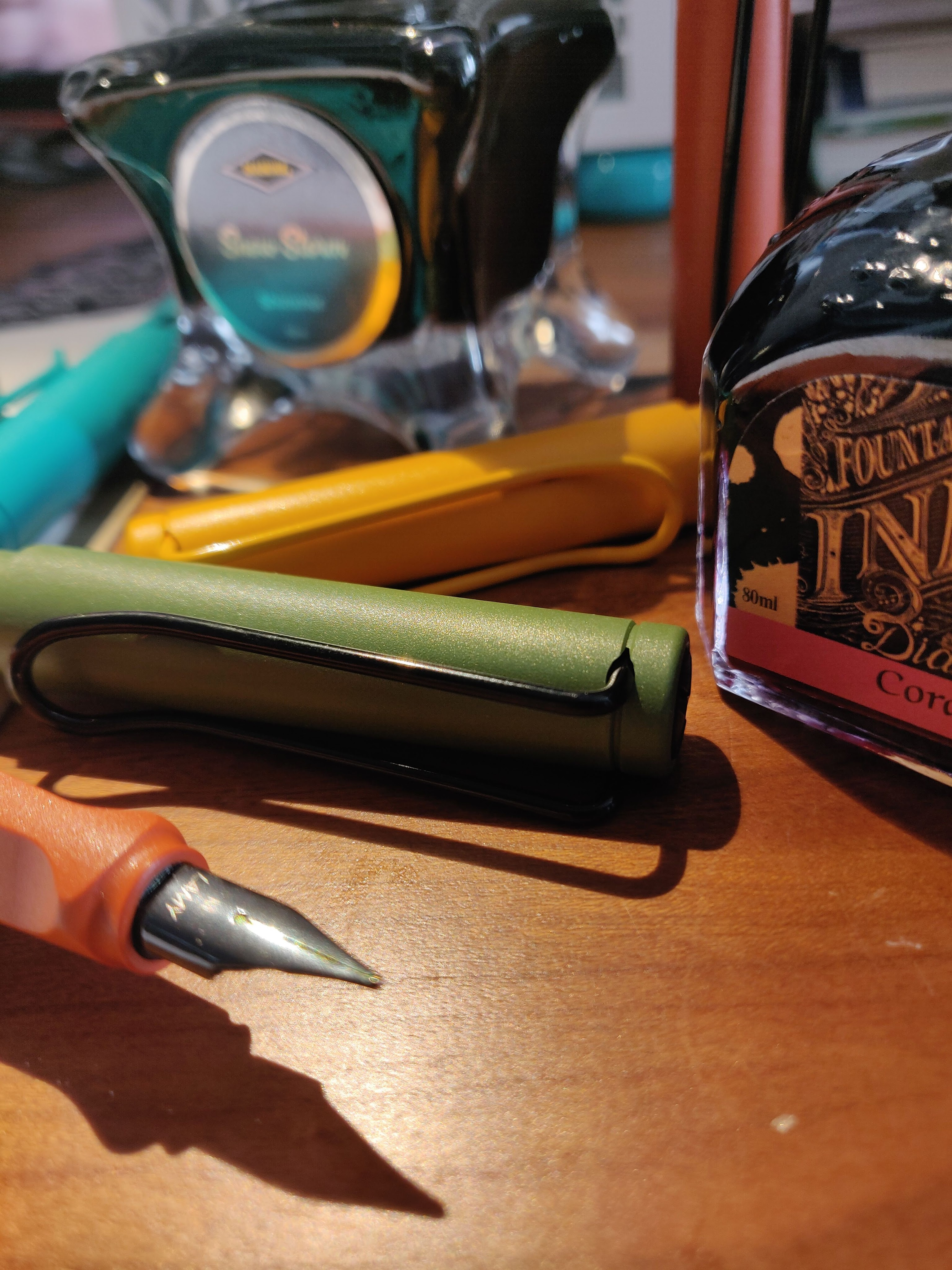 Fountain pens and bottles of ink on a desk.