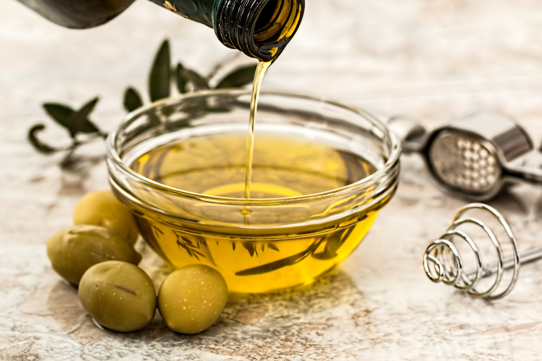 Photo by Pixabay Olive oil being poured from a dark bottle into a small bowl. The bowl is on a counter with a few green olives, olive leaves, and the tools used to press the oil.