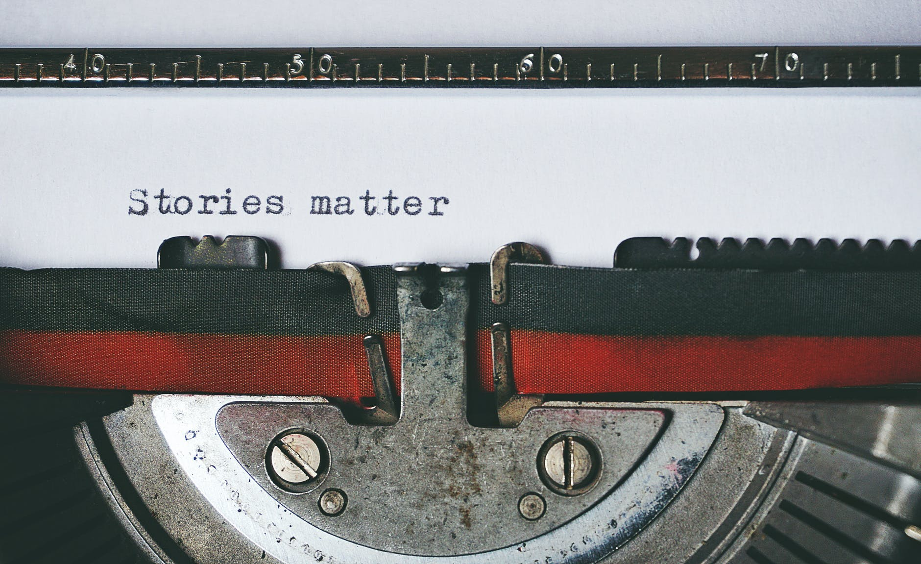 Photo by Suzy Hazelwood. A close-up of a typewriter. The ribbon sits below a line of text on a page. On the paper are the words Stories matter.