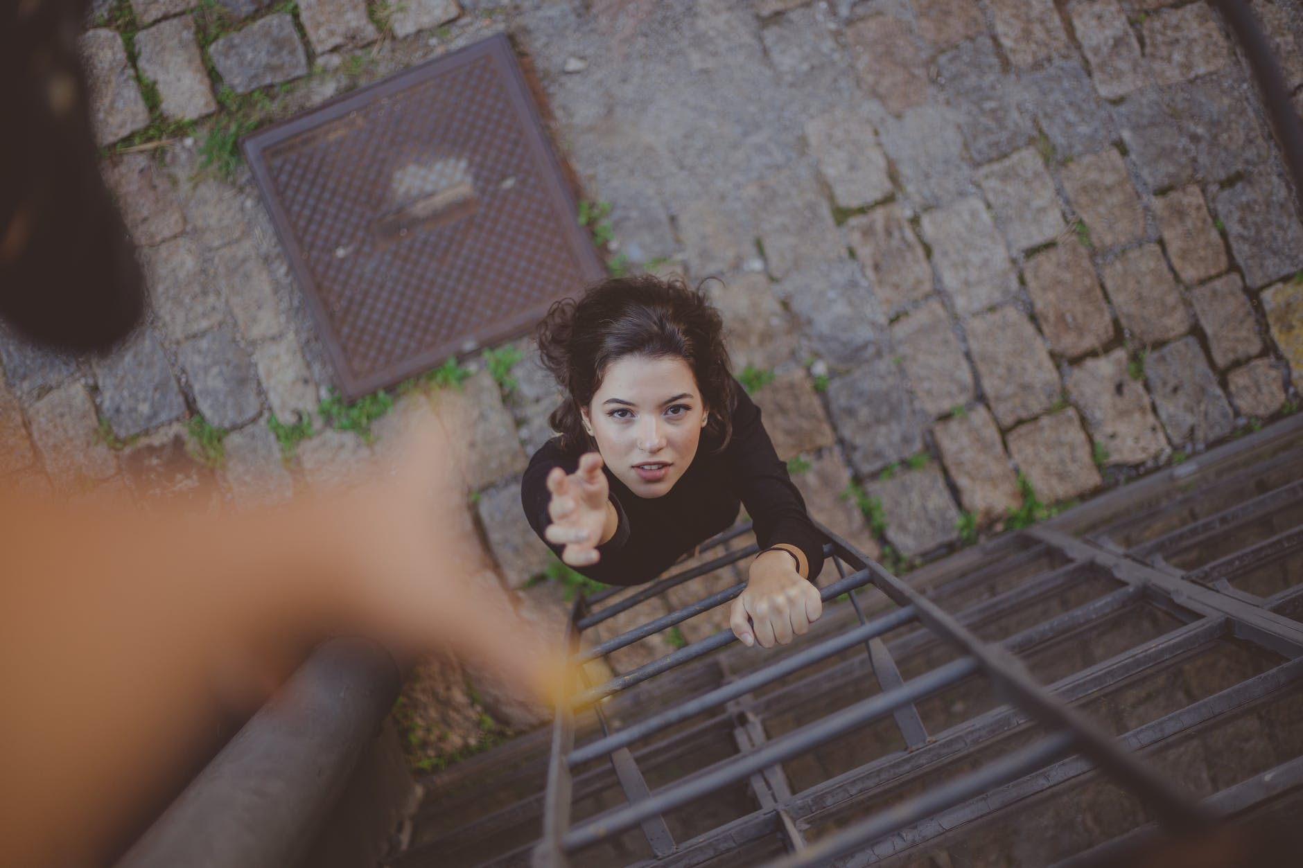 Photo by Samantha Garrote: From the perspective of someone higher up a ladder, extending their hand down to a woman further below, holding her hand up.