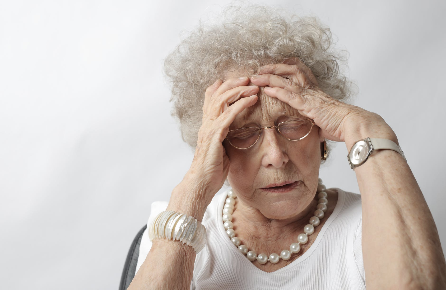 Photo by Andrea Piacquadio. An old woman with her hands holding her head and her eyes closed in exasperation.