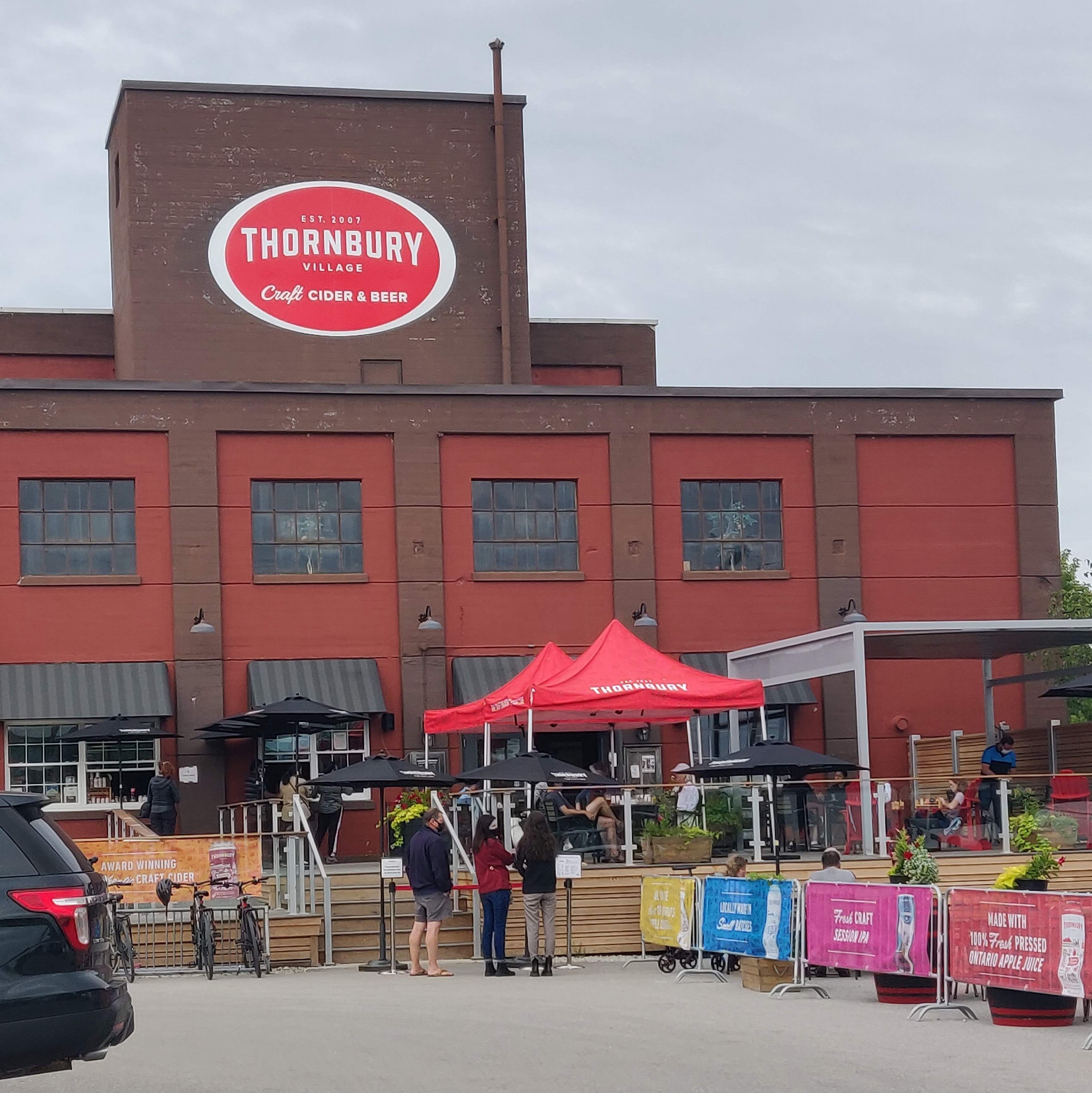 Square brown warehouse-style building with a red oval on a top segment with the Thornbury village Craft cider and beer logo. There are pop-up tents on the patio and a section of the driveway is partitioned off with temporary fencing and large planters for extra seating. There are people seated at the tables, and a few waiting to be seated. There are a few people standing under black awnings ordering bottles to take home.