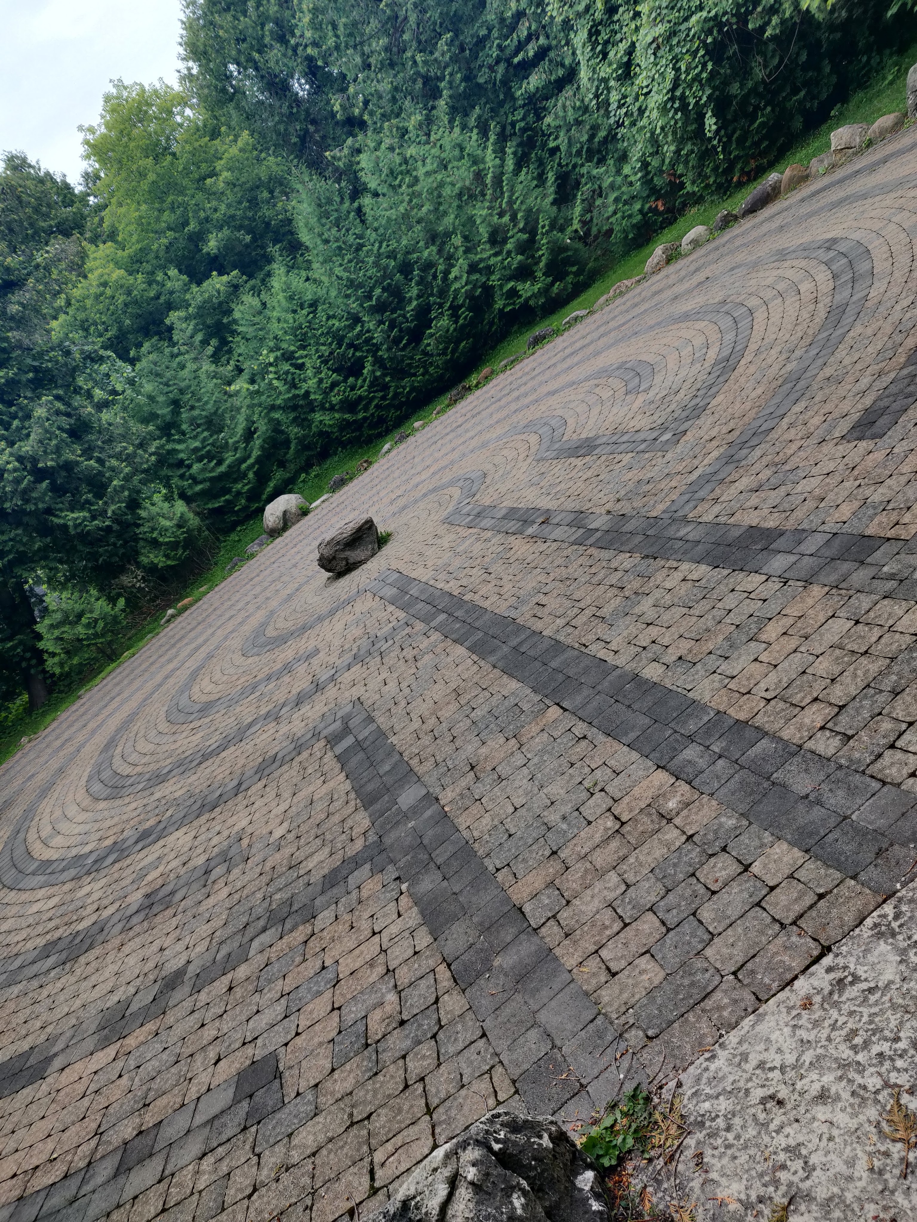 A round labyrinth constructed with cobblestones - gray for the path outline, reddy-brown for the path itself. At the center of the labyrinth there is a small boulder. Beyond the edges of the labyrinth there are cedar trees, tightly planted to form a hedge.