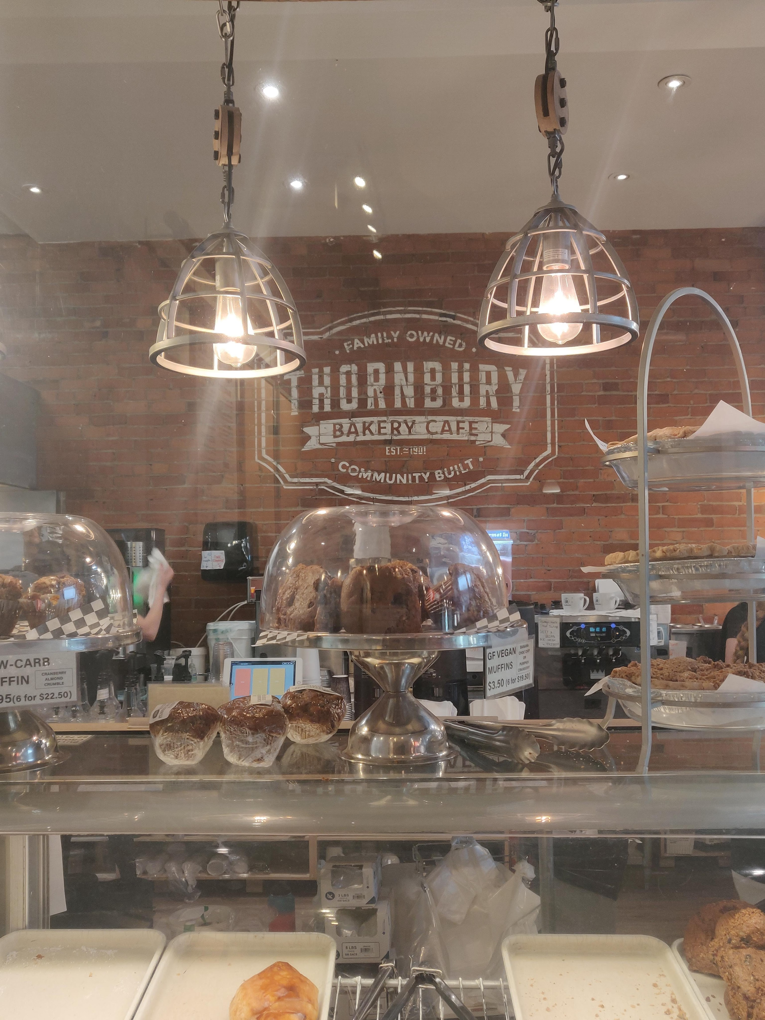 The lower third of the picture is of the pastry display case. There are assorted pastries on separated plates and tongs used to serve them. On top of the glass case there are two domed cake platters containing muffins and a three-tier pie rack. There are two wire framed pendant lights hanging above, and the Thornbury bakery cafe logo is painted on a brick wall behind the counter.