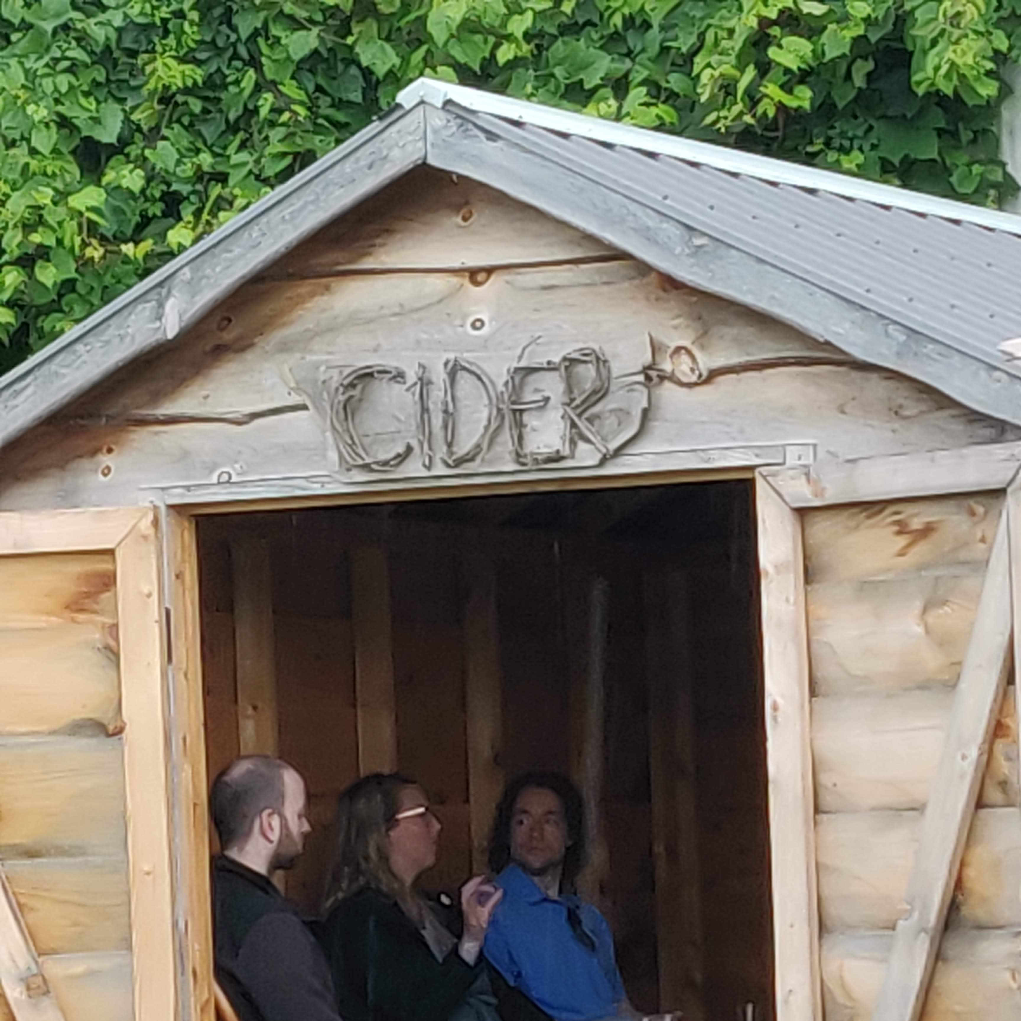 A wood shed with the word Cider crafted out of grape vines over the open door.