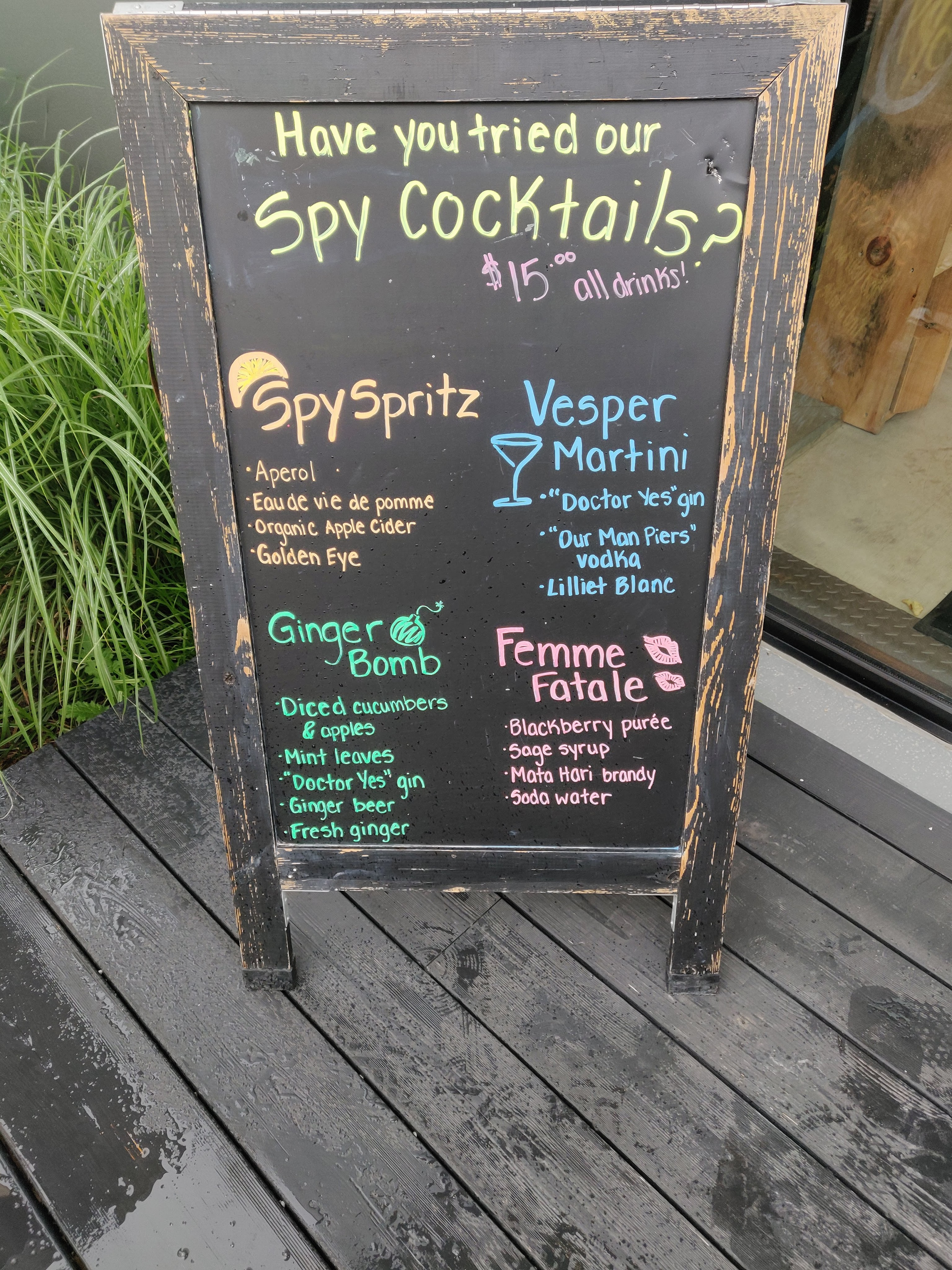 An aged black sandwich board advertising Spy Cocktails: Spy Spritz contains aperol, eau de vie de pomme, organic apple cider, and Golden Eye; Vesper Martini contains Dr. Yes gin, Our Man Piers vodka and Lillet Blanc; Ginger Bomb contains diced cucumbers and apples, mint leaves, Dr. Yes gin, ginger beer and fresh ginger; Femme Fatale contains blackberry puree, sage syrup, mata hari brandy, and soda water. All drinks are $15.