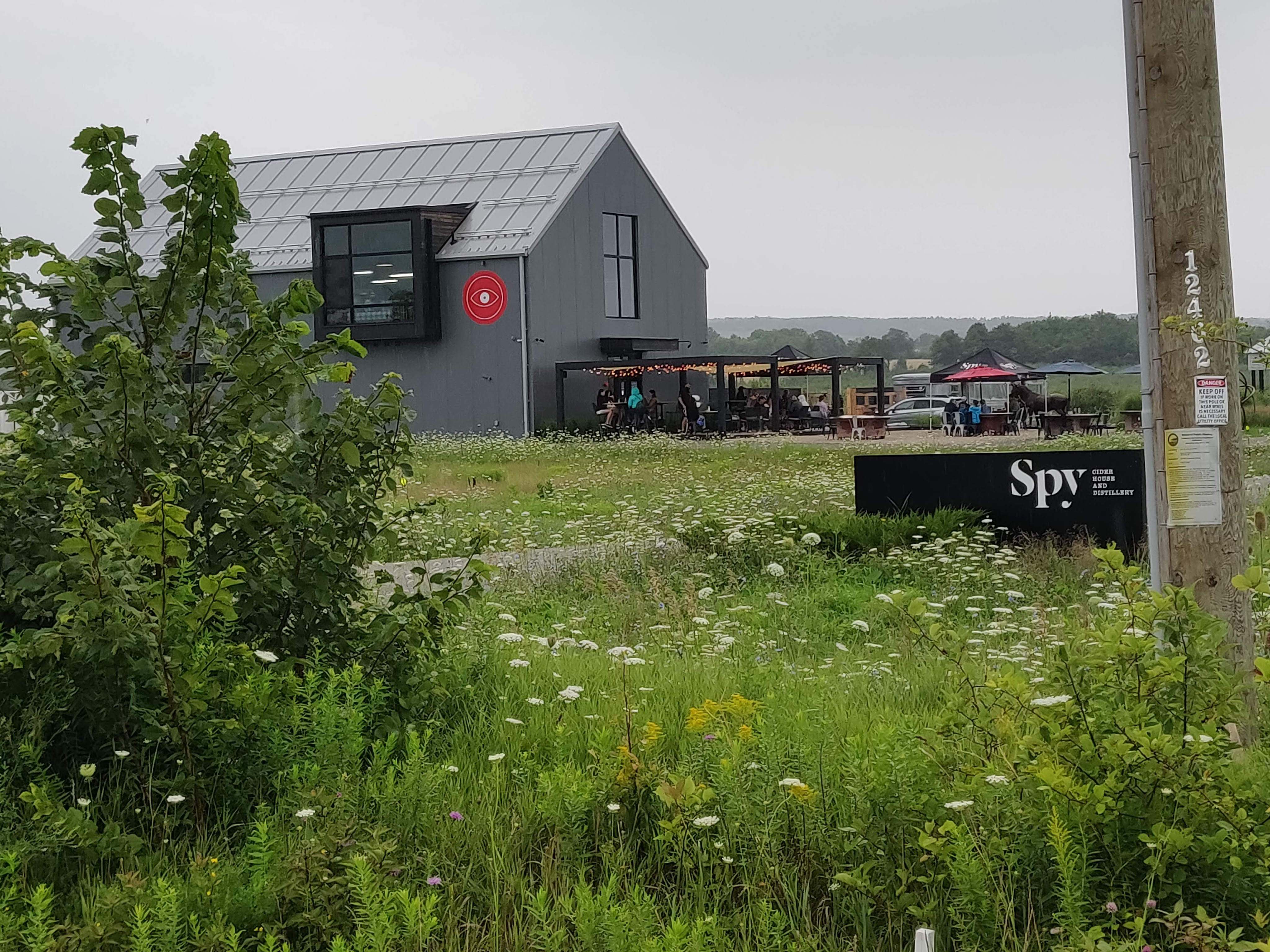 The SPY Cider house and distillery is a gray barh-shaped building in the background with large windows and solar panels on the roof. In the parking lot beside the building there  is a patio set up for patrons. Tables are made with plywood over apple harvest bins with the farm name stamped on the side. The SPY Cider sign is off the side of the driveway. The area between the road and driveway and the parking lot and building are meadow, there are several flowers blooming, including Queen Anne's lace and goldenrod.