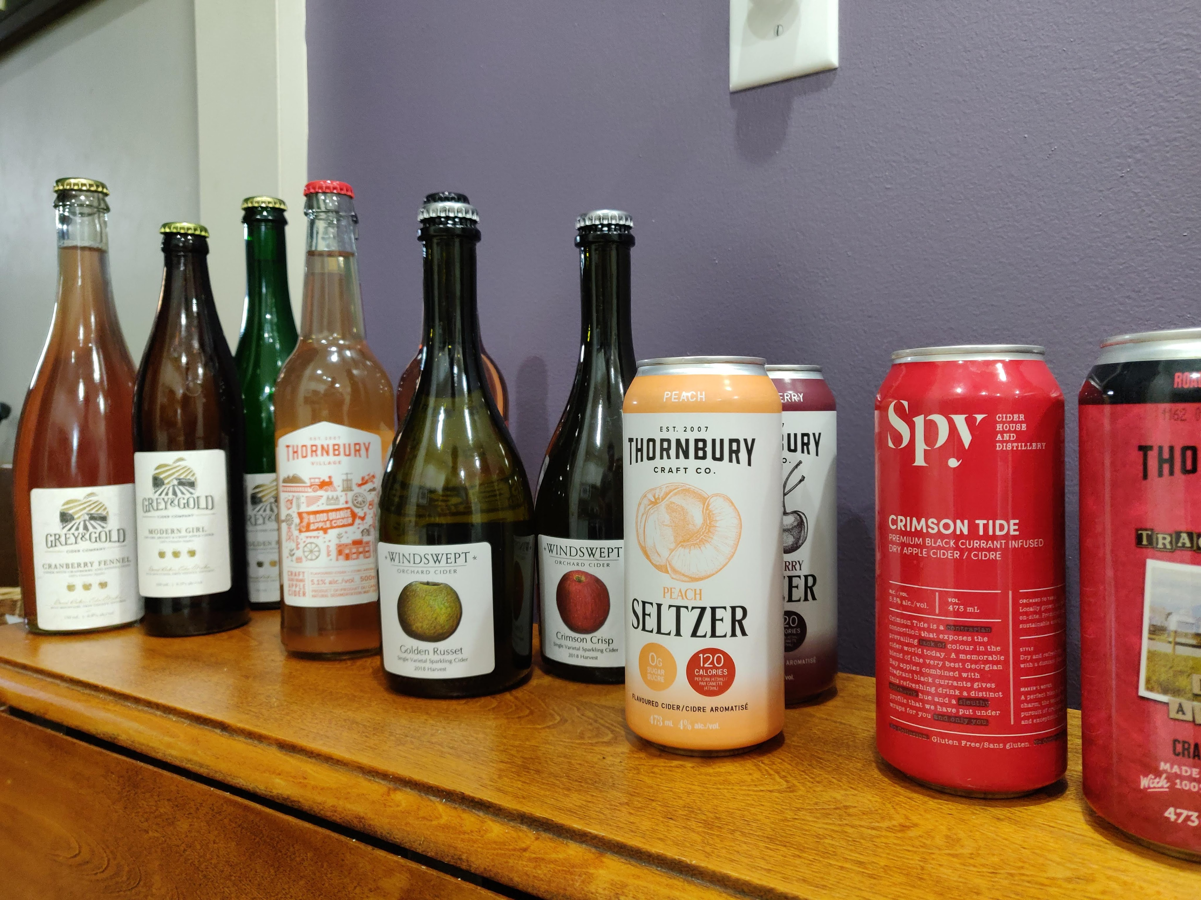 Several bottles and cans of various types of apple cider from Grey and Gold Cider, Thornbury Craft Cider, Windswept Cidery, and Spy Cider.