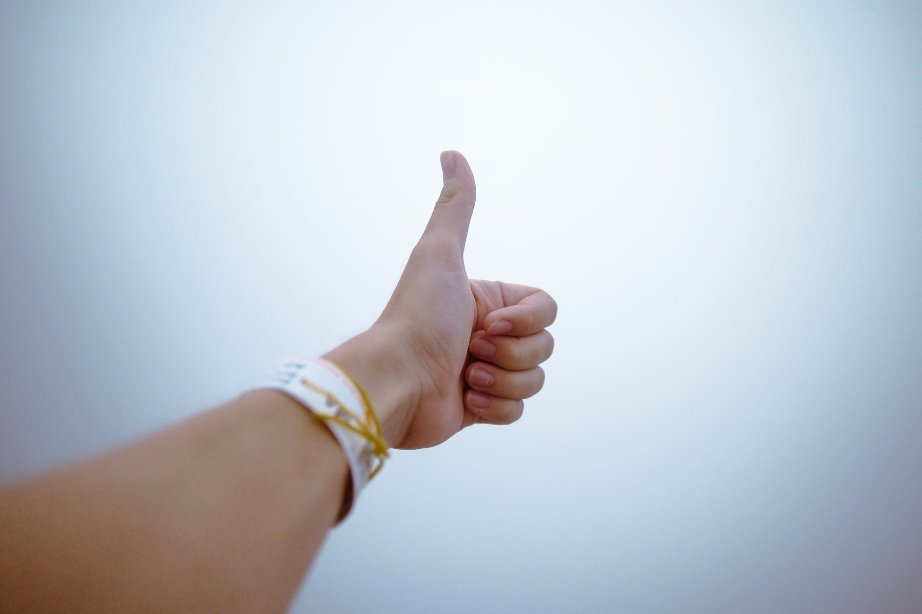 """The photo is taken from the perspective of a person looking at their arm, stretched out in front of them with their thumb extended upward and their fingers curled into their palm, in a """"thumbs up"""" sign."""