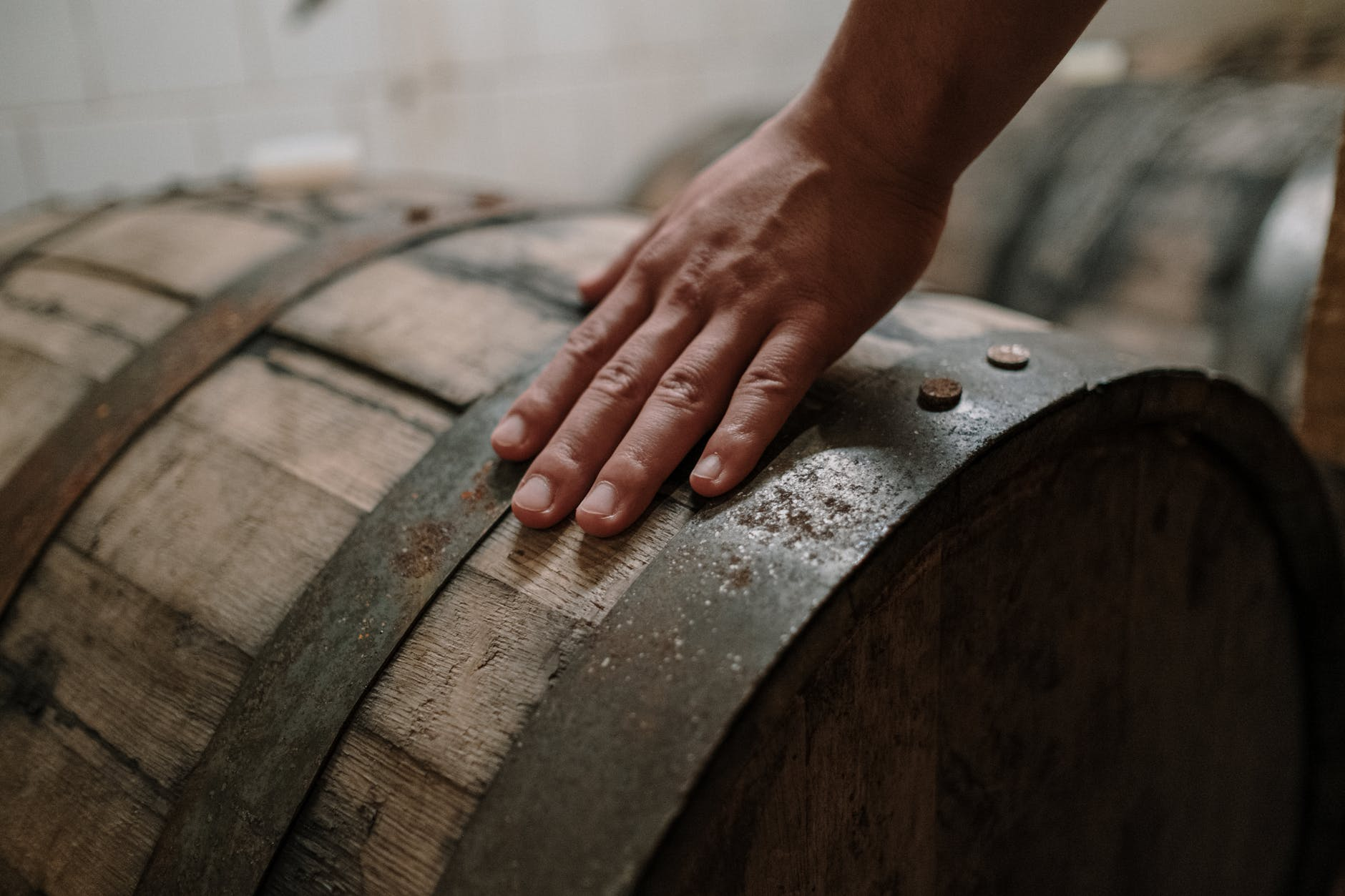 A person's hand, resting on a vintage whiskey barrel, which is resting on it's side beside other barrels.
