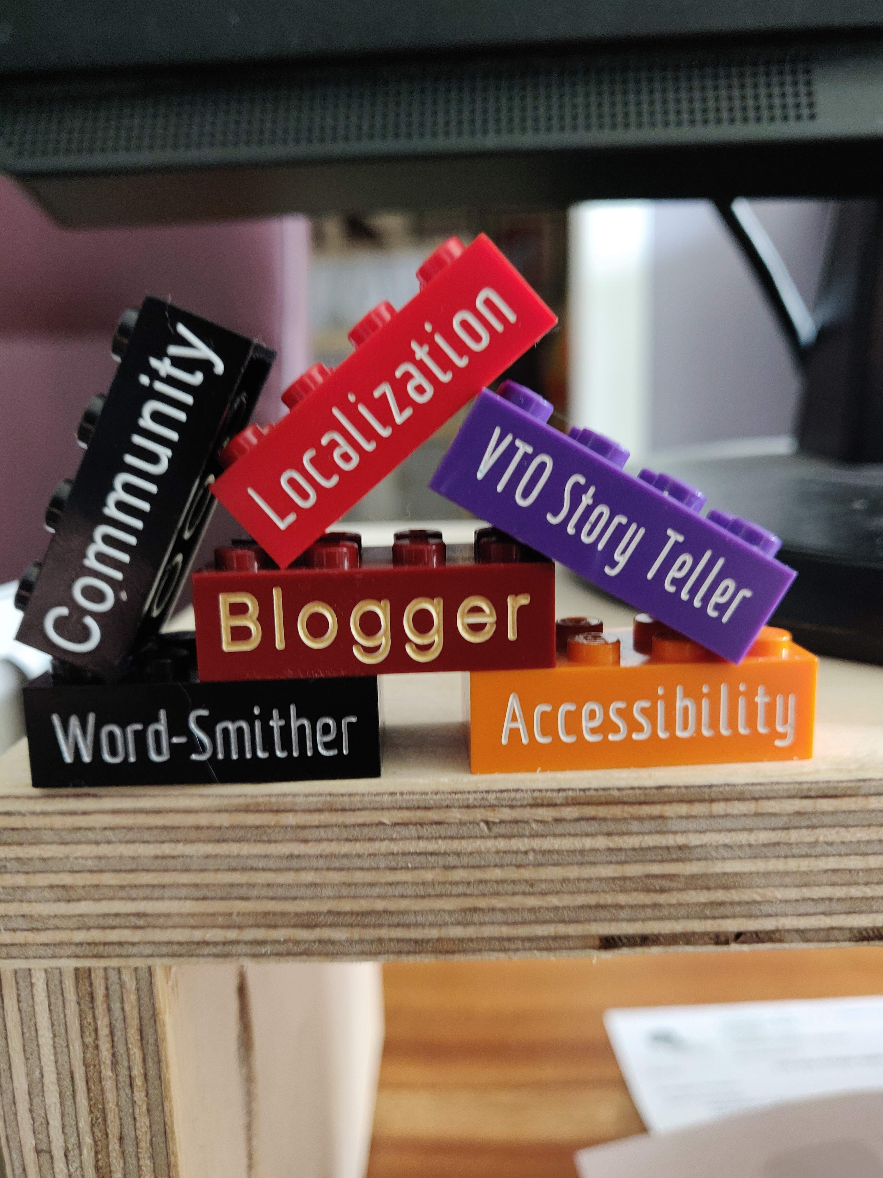 A closeup of Lego blocks with words written on the side of them: Community, Localization, VTO Story Teller, Blogger, Word-Smither, and Accessibility.
