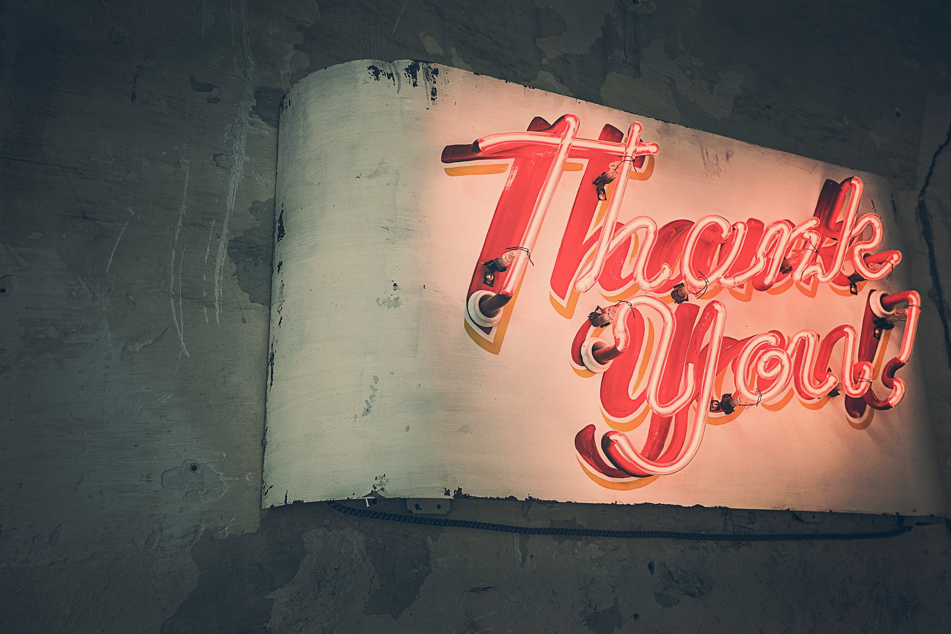 A retro neon sign with the words Thank you in red neon tubes.