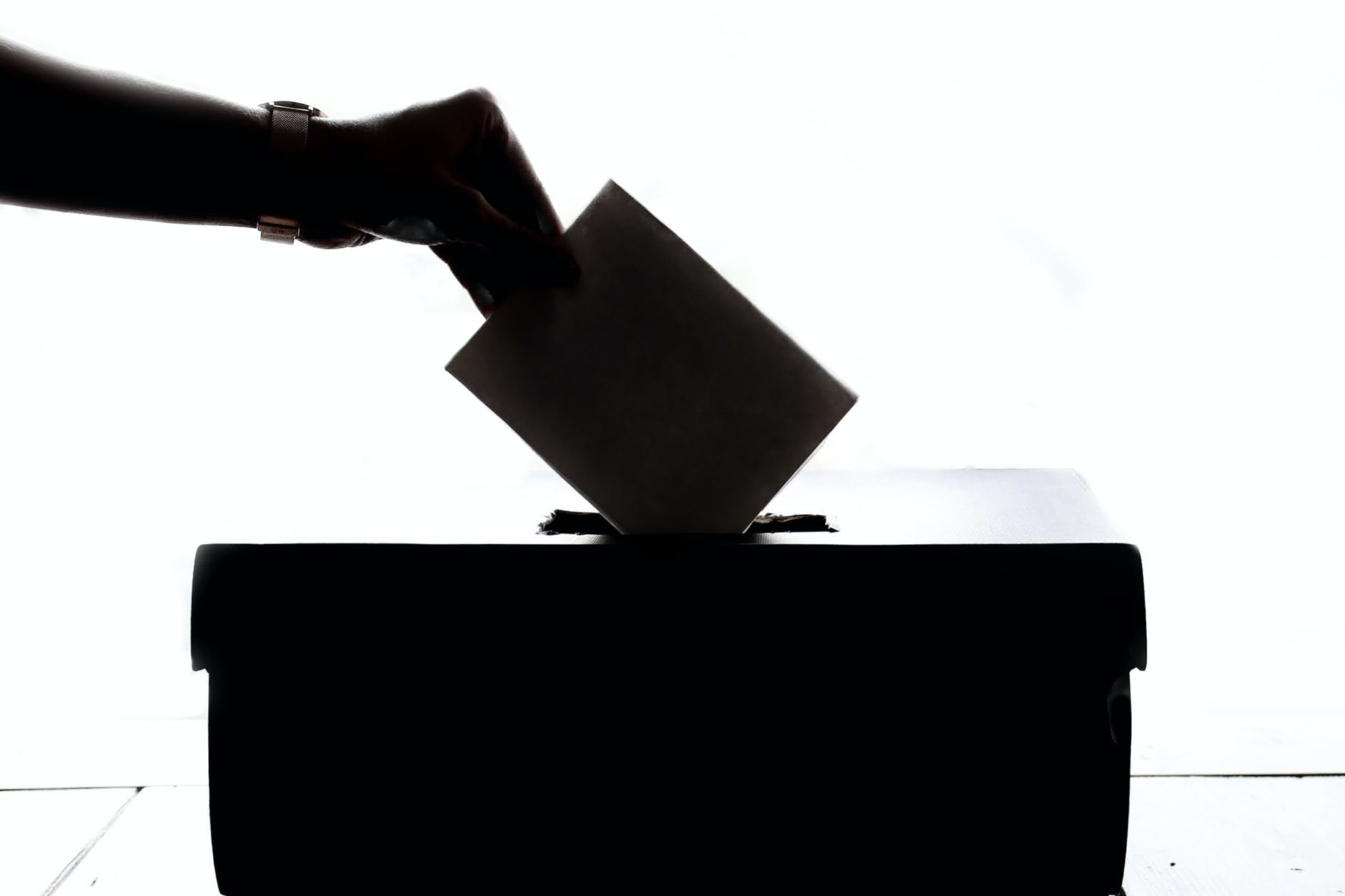 A silhouette of a hand putting a ballot into a box.