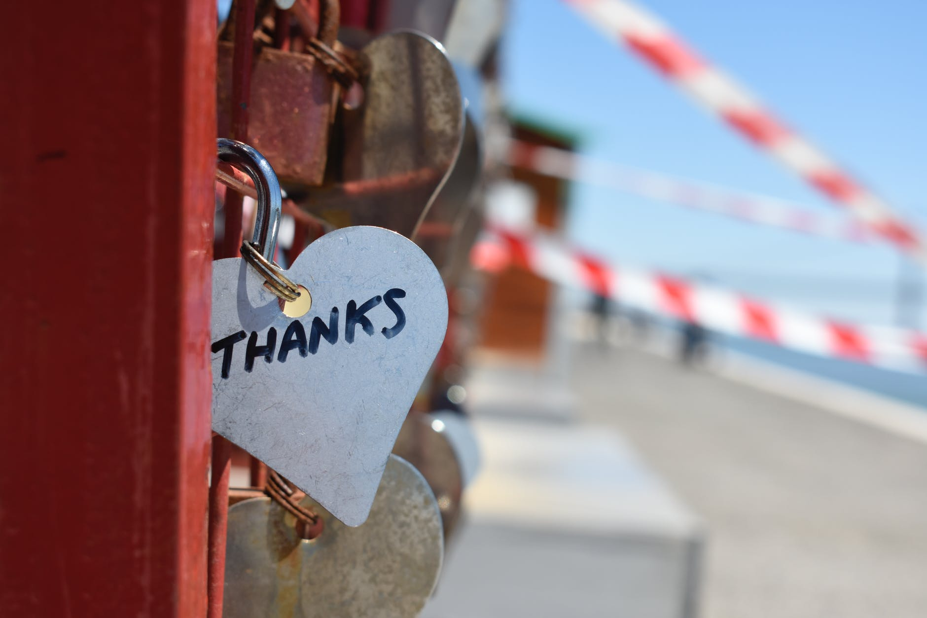 A heart shaped trinket with the words Thanks written on it. The trinket is attached to a padlock that is attached to a red fence.